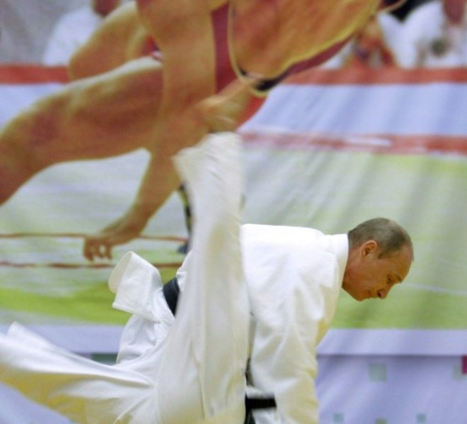 "Russia's Prime Minister Vladimir Putin (top) takes part in a judo training session in front of a poster showing wrestlers fighting at the ""Moscow"" sports complex in St. Petersburg on December 22, 2010.   AFP PHOTO/ RIA-NOVOSTI POOL/ ALEXEY DRUZHININ"