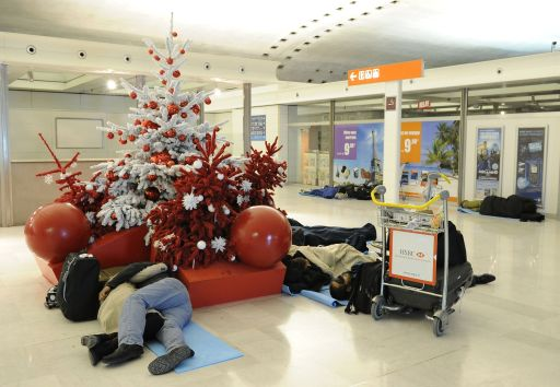 Passengers sleep next to a Christmas tree on December 24, 2010 at Charles de Gaulle airport in Roissy-en-France, outside Paris, as French aviation authorities have canceled half of the flights into and out of Paris Roissy Charles-de-Gaulle airport because of freezing winter conditions. AFP PHOTO / MIGUEL MEDINA