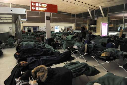 Passengers sleep in camp beds on December 24, 2010 at Charles de Gaulle airport in Roissy-en-France, outside Paris, as French aviation authorities have canceled half of the flights into and out of Paris Roissy Charles-de-Gaulle airport because of freezing winter conditions. AFP PHOTO / MIGUEL MEDINA