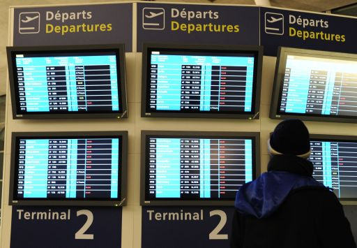 A passenger looks at electronic information boards  on December 24, 2010 at Charles de Gaulle airport in Roissy-en-France, outside Paris, as French aviation authorities have canceled half of the flights into and out of Paris Roissy Charles-de-Gaulle airport because of freezing winter conditions. AFP PHOTO / MIGUEL MEDINA