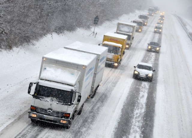 Cars and trucks drive along the snow-covered motorway A7 between Kassel and Hanover near Kassel, central Germany, on December 21, 2010. The snow chaos in Europe has upset the plans of thousands of travelers as ongoing snowfall is paralising all kinds of transport in Germany.   AFP PHOTO / UWE ZUCCHI   GERMANY OUT