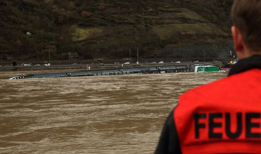 A firefighter looks at a ship loaded with 2400 tons of sulfuric acid that has capsized on the Rhine river near St. Goarshausen, western Germany January 13, 2011. Traffic on the river, a major European shipping artery, was suspended following the accident and two members of the crew were rescued but two others, one German one Czech, are missing according to a water police spokesman. The ship, the Waldhof, measures roughly 110 metres (360 feet) long and was completely turned over, with its keel above the waterline, but it was not immediately clear whether acid had leaked into the river    AFP PHOTO / THOMAS FREY        GERMANY OUT