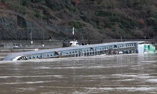 A ship loaded with 2400 tons of sulfuric acid has capsized on the Rhine river next to the Lorelei statue (C) near St. Goarshausen, western Germany, on January 13, 2011. Traffic on the river, a major European shipping artery, was suspended following the accident and two members of the crew were rescued but two others, one German one Czech, are missing according to a water police spokesman. The ship, the Waldhof, measures roughly 110 metres (360 feet) long and was completely turned over, with its keel above the waterline, but it was not immediately clear whether acid had leaked into the river    AFP PHOTO / DANIEL ROLAND