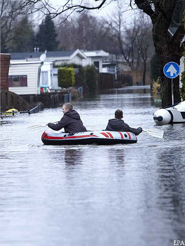 epa02528151 Boys row an inflatable boat along a flooded street in Kerkdriel, The Netherland on 13 January 2011 where reports state taht around 250 mobile homes are flooded by high water from the river De Maas.  EPA/WIM HOLLEMANS