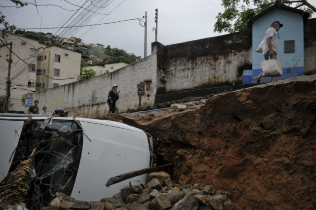 Residents walks by a crater that engulfed a vehicle in a destroyed street in Nova Friburgo, Rio de Janeiro, Brazil, on January 16, 2011. The Brazilian military sent troops and helicopters Sunday to rescue stranded survivors of floods and landslides that killed more than 625 people but the operation was stymied by more bad weather. AFP PHOTO/Mauricio LIMA