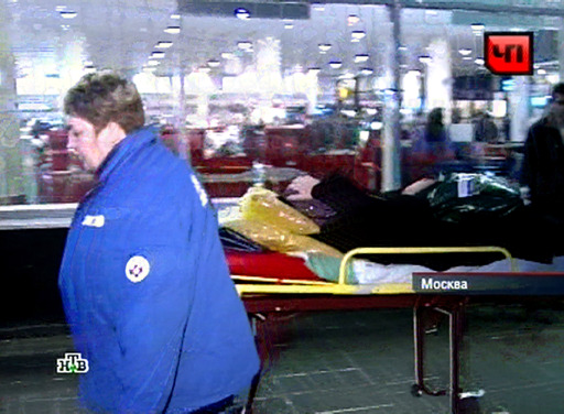 A TV grab taken from Russian TV channel NTV shows paramedics carrying a person injured by a blast toward an ambulance at Moscow's Domodedovo international airport on January 24, 2011, shortly after an explosion. A suspected suicide bombing on January 24 killed at least 31 people and wounded over 100 at the airport in an attack described by investigators as an act of terror. Eyewitnesses, who spoke to Russian radio, described a scene of carnage after the blast ripped through the baggage claims section of the arrivals hall at Russia's largest airport. AFP PHOTO/NTV