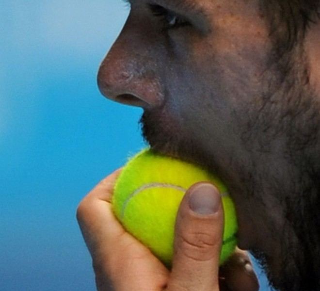 Stanislas Wawrinka of Switzerland holds a tennis ball in his mouth during his men's singles quarter-final match against Roger Federer of Switzerland on the ninth day of the Australian Open tennis tournament in Melbourne on January 25, 2011.         Federer leads by two sets to nil as play continues.                            IMAGE STRICTLY RESTRICTED TO EDITORIAL USE    ?    STRICTLY NO COMMERCIAL USE      AFP PHOTO/Greg WOOD