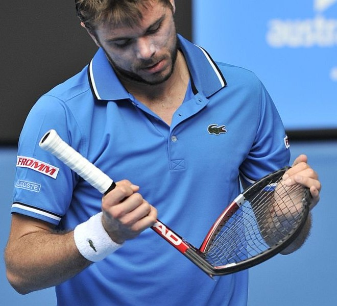 Stanislas Wawrinka of Switzerland folds up his broken racquet after smashing it on the ground in reaction to losing a point during his quarter-final men's singles match against Roger Federer of Switzerland on the ninth day of the Australian Open tennis tournament in Melbourne on January 25, 2011.  Federer won 6-1, 6-3, 6-3.  IMAGE STRICTLY RESTRICTED TO EDITORIAL USE ? STRICTLY NO COMMERCIAL USE   AFP PHOTO / PAUL CROCK