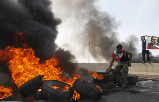 Lebanese supporters of the Future Movement burn tires during a demonstration in support of the caretaker prime minister Saad Hariri (banner R) on the outskirts of the coastal city of Sidon, south of Beirut on January 25, 2011, as hundreds of people converged on the northern city of Tripoli to take part in a 'day of rage' over the likely appointment as prime minister of Hezbollah-backed tycoon Najib Mikati. AFP PHOTO/MAHMOUD ZAYAT