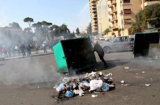 A Lebanese woman attempts to push a burning garbage container as supporters of the Future Movement gather in a neighborhood in the capital Beirut during a demonstration in support of the caretaker prime minister Saad Hariri on January 25, 2011, as hundreds of people converged on the northern city of Tripoli to take part in a 'day of rage' over the likely appointment as prime minister of Hezbollah-backed tycoon Najib Mikati. AFP PHOTO/ANWAR AMRO
