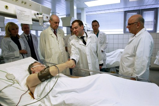 "Russian President Dmitry Medvedev (C) shakes hand with a man wounded in the January 24 blast at Moscow's Domodedovo airport, on January 25, 2011 at Sklifovski hopistal in Moscow. Dmitry Medvedev vowed today to step up security at the 2014 Winter Olympic Games in Sochi after a bomb blast at a Moscow airport killed 35 people and injured scores more. President Dmitry Medvedev on Tuesday vowed to hunt down Islamist militants and lashed out at ""anarchic"" security lapses after a suicide bomber slaughtered 35 people in arrivals at Russia's main airport. (L is Russian Public Health and Social Development Minister Tatyana Golikova, 2nd L is Moscow Mayor Sergei Sobyanin, and at R is the director of the hospital, Anzor Hubutiya). AFP PHOTO / RIA NOVOSTI"