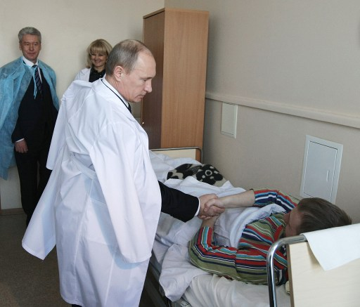 "Russian Prime Minister Vladimir Putin (2nd R), flanked by Russian Public Health and Social Development Minister Tatyana Golikova (R in the background) and Moscow Mayor Sergei Sobyanin (L in the background), shakes hands with a man wounded in the January 24 blast at Moscow's Domodedovo airport, as pays a visit to the Vishnevsky Surgical Institute on January 25, 2011 in Moscow. Russian President Dmitry Medvedev vowed today to step up security at the 2014 Winter Olympic Games in Sochi after a bomb blast at a Moscow airport killed 35 people and injured scores more. President Dmitry Medvedev on Tuesday vowed to hunt down Islamist militants and lashed out at ""anarchic"" security lapses after a suicide bomber slaughtered 35 people in arrivals at Russia's main airport. AFP PHOTO / RIA NOVOSTI - ALEXEI NIKOSKY"