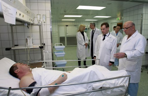 "Russian President Dmitry Medvedev (3rd R) listens to a doctor's explanations as they stand in front of a man wounded in the January 24 blast at Moscow's Domodedovo airport, on January 25, 2011 at Sklifovsky hopistal in Moscow. Dmitry Medvedev vowed today to step up security at the 2014 Winter Olympic Games in Sochi after a bomb blast at a Moscow airport killed 35 people and injured scores more. President Dmitry Medvedev on Tuesday vowed to hunt down Islamist militants and lashed out at ""anarchic"" security lapses after a suicide bomber slaughtered 35 people in arrivals at Russia's main airport. (. AFP PHOTO / RIA NOVOSTI"