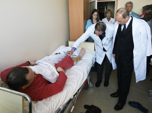"Russian Prime Minister Vladimir Putin (R), flanked by Moscow Mayor Sergei Sobyanin (R in the background), shakes hands with a man wounded in the January 24 blast at Moscow's Domodedovo airport, as he pays a visit to the Vishnevsky Surgical Institute on January 25, 2011 in Moscow. Russian President Dmitry Medvedev vowed today to step up security at the 2014 Winter Olympic Games in Sochi after a bomb blast at a Moscow airport killed 35 people and injured scores more. President Dmitry Medvedev on Tuesday vowed to hunt down Islamist militants and lashed out at ""anarchic"" security lapses after a suicide bomber slaughtered 35 people in arrivals at Russia's main airport. AFP PHOTO / RIA NOVOSTI - ALEXEI NIKOSKY"