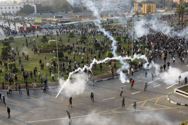 Egyptian demonstrators clash with Egyptian police in central Cairo during a protest to demand the ouster of President Hosni Mubarak and calling for reforms on January 25, 2011. The protesters, carrying flags and chanting slogans against the government, rallied in a protest inspired by the uprising in Tunisia which led to the ouster of Zine El Abidine Ben Ali.  AFP PHOTO/MOHAMMED ABED , Tear gas smoke fired by Egyptian police is seen as demonstrators gather in central Cairo to demand the ouster of President Hosni Mubarak and calling for reforms on January 25, 2011. The protesters, carrying flags and chanting slogans against the government, rallied in a protest inspired by the uprising in Tunisia which led to the ouster of Zine El Abidine Ben Ali.  AFP PHOTO/MOHAMMED ABED