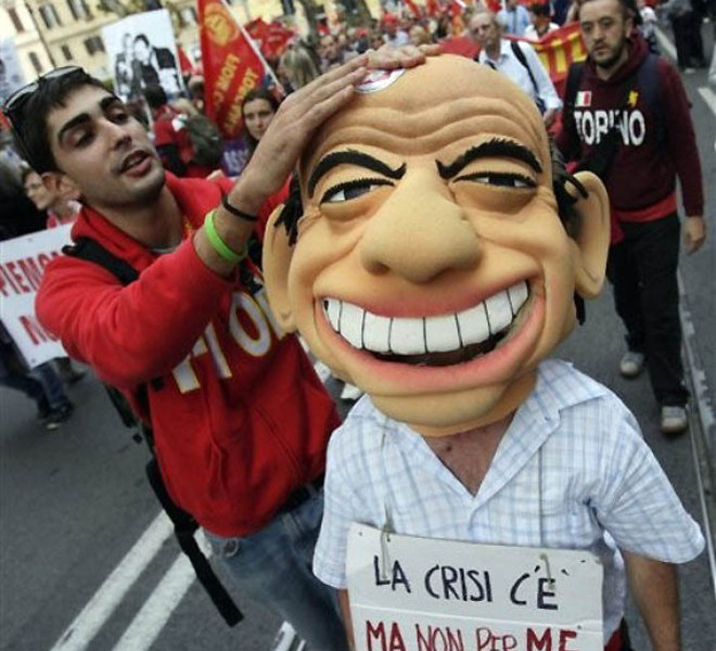 "Italian Metal Workers of the FIOM (Federation of Metal Employees and Workers) Labor Union parade in downtown Rome, Saturday, Oct. 16, 2010, during a demonstration staged to protest against Government's labor policy. Demonstrator in foreground is putting a sticker on the head of a puppet mocking Italian premier Silvio Berlusconi. The banner on the puppet reads: ""La crisi c'e' ma non per me"" (There is crisis but not for me). (AP Photo/Alessandra Tarantino)"