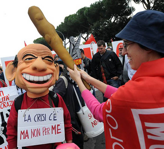 "A demonstrator knocks on the head another demonstrator, wearing a mask of Italian Prime Minister Silvio Berlusconi (L) and wearing a placard reading ""There is a crisis, but not for me"", during a protest in defence of labour contracts and against the government on October 16, 2010 in central Rome.  Thousands of people marched in Rome at a trade union protest in defence of labour contracts and against the government, with many leftist opposition supporters also joining in.  AFP PHOTO / ALBERTO PIZZOLI (Photo credit should read ALBERTO PIZZOLI/AFP/Getty Images)"