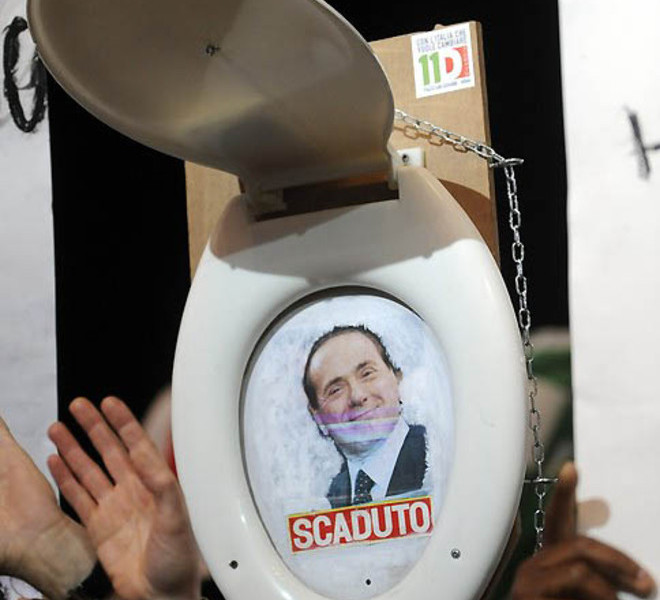 "A demonstrator holds a toilet seat with a photo of Italian Prime Minister Silvio Berlusconi reading ""expiried"" during a march to protest against Silvio Berlusconi's government called by the left-wing Democratic Party (PD) on December 11, 2010 in Rome. Berlusconi faces a knife-edge confidence vote in both houses of parliament on December 13 that could trigger his downfall or see the resilient Italian leader bounce back once again.   AFP PHOTO / TIZIANA FABI (Photo credit should read TIZIANA FABI/AFP/Getty Images)"
