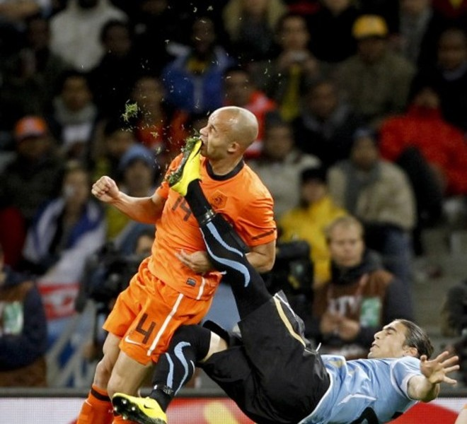 "RESTRICTED TO EDITORIAL USE - MANDATORY CREDIT ""AFP PHOTO / REUTERS / MIKE HUTCHINGS"" - NO MARKETING NO ADVERTISING CAMPAIGNS - DISTRIBUTED AS A SERVICE TO CLIENTS -- NO ARCHIVE -- RESTRICTED TO SUBSCRIPTION USE This handout picture released on February 11, 2011 by World Press Photo shows Netherlands' Demy de Zeeuw (L) being kicked in the face by Uruguay?s Martin Caceres during their World Cup semi-final match in Cape Town, on July 6, 2010. Hutchings won the 1st Prize Sport Single category in the World Press Photo 2010.   AFP PHOTO / REUTERS / MIKE HUTCHINGS"