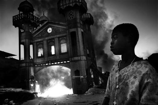 "RESTRICTED TO EDITORIAL USE - MANDATORY CREDIT ""AFP PHOTO / CONTRASTO / RICCARDO VENTURI"" - NO MARKETING NO ADVERTISING CAMPAIGNS - DISTRIBUTED AS A SERVICE TO CLIENTS -- NO ARCHIVE -- RESTRICTED TO SUBSCRIPTION USE This handout picture released on February 11, 2011 by World Press photo shows a boy standing by the burning old Iron Market in Port-au-Prince, Haiti, on January 18, 2010. Riccardo Venturi won the General News Singles category in the World Press Photo 2010.   AFP PHOTO / CONTRASTO / RICCARDO VENTURI"