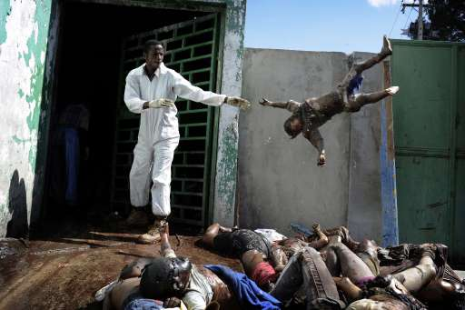 A man throws a dead body at the morgue of the general hospital, January 15, 2010 at Port Au Prince following the 7.0-magnitude quake on January 12. More than 50,000 people were killed and 250,000 injured by this week's earthquake, which also left nearly 1.5 million homeless, a Haitian minister said. After three days of Haitians being left to fend mostly for themselves in one of the world's poorest countries. Olivier Laban-Mattei won the 1st prize General News Stories category in the World Press Photo 2010.     AFP PHOTO / OLIVIER LABAN-MATTEI