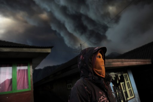 ADDING DETAIL (FILES) File photo taken by AFP photographer Christophe Archambault on December 24, 2010 shows an Indonesian man wearing a mask to avoid inhaling ash as he stands in the ash-covered village of Cemoro Lawang near the active Mount Bromo volcano in the east of Indonesia's central Java island. Archambault took third prize in the 'Stories' section of the World Press Photo 'Nature' category for a series on the erupting volcano Bromo, in Java. Organisers said a record number of 108,059 images was submitted for this year's contest. A total of 5,847 photographers took part, representing 125 different nationalities. AFP PHOTO / FILES / Christophe ARCHAMBAULT