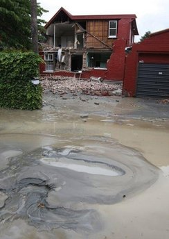 Liquification bubbles to the surface in front of a damaged house  in Christchurch, New Zealand, Tuesday, Feb. 22, 2011. A powerful earthquake collapsed buildings at the height of a busy workday killing and trapping dozens of people in one of the country's worst natural disasters. (AP Photo/NZPA/Ashburton Guardian, Kirsty Graham) NEW ZEALAND OUT, NO ARCHIVES, NO SALES