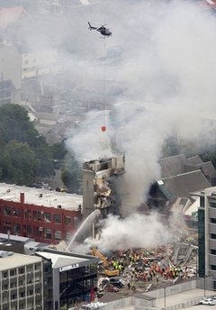 ADDS NAME OF THE COLLAPSED BUILDING - Rescue workers and a helicopter work to extinguish a fire at a collapsed building of King's Education in central Christchurch, New Zealand, Tuesday, Feb. 22, 2011. A powerful earthquake collapsed buildings at the height of a busy workday killing at least 65 people and trapping dozens in one of the country's worst natural disasters. Several among a group of 23 Japanese exchange students and teachers at King's Education were still unaccounted for. (AP Photo/New Zealand Herald, Mark Mitchell) NEW ZEALAND OUT, AUSTRALIA OUT