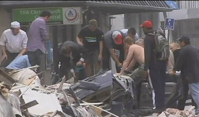 In this image made from video run by New Zealand's TVNZ,  people stand in the rubble of collapsed building following a strong earthquake in Christchurch, New Zealand Tuesday, Feb. 22, 2011. The strong, 6.3-magnitude earthquake rocked the southern New Zealand city of Christchurch on Tuesday, seriously injuring people and damaging buildings throughout the city. (AP Photo/TVNZ via Associated Press Television News) NEW ZEALAND OUT, TV OUT