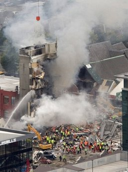 ALTERNATE CROP OF NZH802 - Rescue workers work to extinguish a fire at a collapsed building in central Christchurch, New Zealand, Tuesday, Feb. 22, 2011. A powerful earthquake collapsed buildings at the height of a busy workday Tuesday, killing and trapping dozens in one of the country's worst natural disasters. (AP Photo/New Zealand Herald, Mark Mitchell) NEW ZEALAND OUT, AUSTRALIA OUT