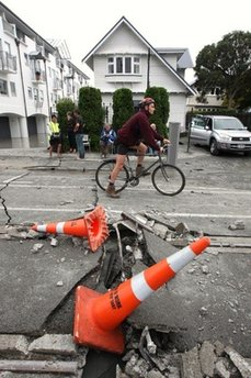 A man rides his bicycle on a damaged road in Christchurch, New Zealand, Tuesday, Feb. 22, 2011. A powerful earthquake collapsed buildings at the height of a busy workday killing and trapping dozens of people in one of the country's worst natural disasters. (AP Photo/NZPA/Ashburton Guardian, Kirsty Graham) NEW ZEALAND OUT, NO ARCHIVES, NO SALES