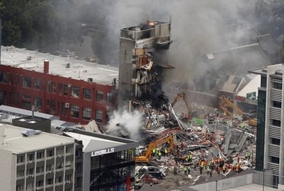 Rescue workers work to extinguish a fire at a collapsed building in central Christchurch, New Zealand, Tuesday, Feb. 22, 2011. A powerful earthquake collapsed buildings at the height of a busy workday killing and trapping dozens of people in one of the country's worst natural disasters. (AP Photo/New Zealand Herald, Mark Mitchell) NEW ZEALAND OUT, AUSTRALIA OUT