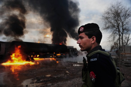 A Pakistani policeman stands guard next to burning NATO oil tankers following an attack at a terminal on the outskirts of Peshawar on February 25, 2011. Militants in northwestern Pakistan blew up at least 11 tankers carrying fuel for NATO troops in neighbouring Afghanistan and shot dead four people, police said. AFP PHOTO/ A. MAJEED