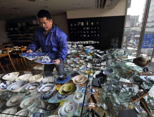 The owner of a ceramic shop checks his damaged wares following the massive 8.9-magnitude earthquake in Tokyo on March 11, 2011. The huge earthquake shook Japan, unleashing a powerful tsunami that sent ships crashing into the shore and carried cars through the streets of coastal towns.   AFP PHOTO / Yoshikazu TSUNO