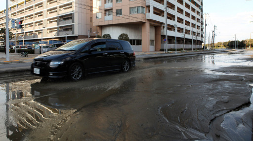 A lone car rests among the remain of water on a street in Chiba city, suburban Tokyo on March 11, 2011.  A massive 8.8-magnitude earthquake shook Japan, unleashing a powerful tsunami that sent ships crashing into the shore and carried cars through the streets of coastal towns. AFP PHOTO / JIJI PRESS