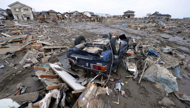 A structures lies on the road after being destroyed by the tsunami, close to the airport in Sendai on March 14, 2011.  A new explosion at a nuclear plant in nearby Fukushima prefecture hit punch-drunk Japan on March 14 as it raced to avert a reactor meltdown after a quake-tsunami disaster that is feared to have killed more than 10,000 people.         AFP PHOTO / Philippe Lopez