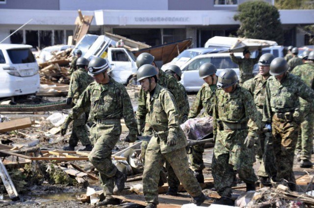Rescue crews work on a devastated building as they look for victims after the recent tsunami and earthquake in Natori City in Miyagi prefecture on March 14, 2011.  A new explosion at a nuclear plant in nearby Fukushima prefecture hit punch-drunk Japan on March 14 as it raced to avert a reactor meltdown after a quake-tsunami disaster that is feared to have killed more than 10,000 people.     AFP PHOTO/MIKE CLARKE