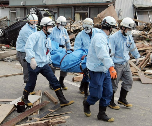 Rescue team members carry a dead body at Ofunato city in Iwate city on March 14, 2011. A new explosion at a nuclear plant hit punch-drunk Japan on March 14 as it raced to avert a reactor meltdown after a quake-tsunami disaster that is feared to have killed more than 10,000 people.   AFP PHOTO / JIJI PRESS