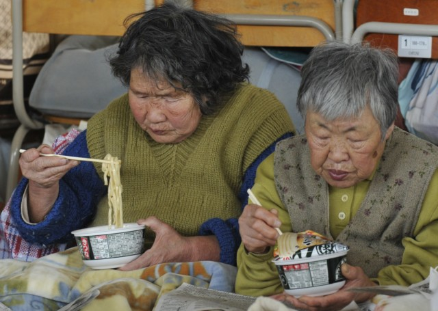 Evacuees eat instant noodles for lunch at a shelter in Rikuzentakata in Iwate prefecture on March 18, 2011, one week after a massive earthquake and tsunami ravaged northeastern Japan. Japan battled a nuclear and humanitarian crisis on March 18 as engineers worked to restore power to a stricken atomic plant, while the toll of dead and missing from the quake and tsunami topped 16,000. AFP PHOTO / KAZUHIRO NOGI