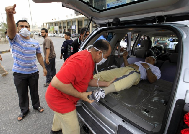 Bahraini anti-government protesters place concrete roadblocks on the highway leading to Pearl Square in Manama on March 14, 2011. Armoured troops rolled into Bahrain from neighbouring Saudi Arabia to help restore order in the strategic Gulf kingdom, where pro-democracy demonstrators have shut down the financial centre. AFP PHOTO/JAMES LAWLER DUGGAN , Tear gas is fired by Bahraini police explode among the protestors gathered close to Pearl Square, the epicentre of anti-government protests, the first time since demonstrators began an anti-regime sit-in there last month on March 13, 2011, in Manama. Almost a month into protests calling for deep political change in Bahrain, anti-government demonstrators and the Gulf kingdom's rulers appear to be at an impasse, with neither side backing down. AFP PHOTO/STR , A protester over come by tear gas is ferried away as Bahraini police fire tear gas at protesters in Pearl Square, the epicentre of anti-government protests, the first time since demonstrators began an anti-regime sit-in there last month on March 13, 2011, in Manama. Almost a month into protests calling for deep political change in Bahrain, anti-government demonstrators and the Gulf kingdom's rulers appear to be at an impasse, with neither side backing down. AFP PHOTO/ADAM JAN
