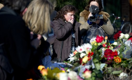 Mourners look at flowers left in memory of Knut the polar bear at his enclosure at the Berlin zoo (Zoologischer Garten) March 20, 2011. Germany was in stunned mourning after the sudden and premature death of Knut, Berlin's world-famous polar bear, who died on March 19, 2011, at the end of what animal welfare groups said was an unhappy, short life. AFP PHOTO / JOHANNES EISELE