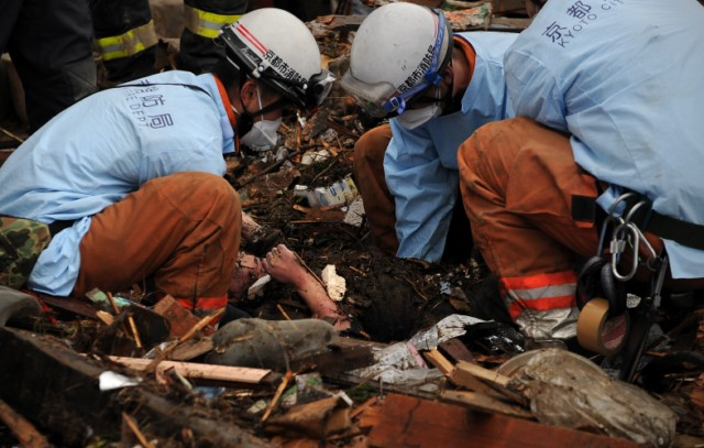 Japanese firemen from the Kyoto City department recover the body of a victim from the wreckage in Minamisanriku, Myagi province, on March 21, 2011, 10 days after a massive earthquake and tsunami ravaged northeastern Japan. The natural disaster -- Japan's deadliest since 1923 -- has left 8,649 people dead and 13,262 missing, after entire communities were swept away by the horrific tsunami or levelled by the record 9.0-magnitude quake.  Miyagi prefecture was worst hit by the quake and tsunami, with a confirmed death toll of 4,882 so far.  AFP PHOTO / PHILIPPE LOPEZ
