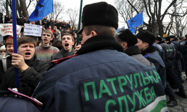 People shout slogans and hold banner as they try to block the traffic in front of policemen during a rally near the Ukraine's Cabinet of the Ministers in Kiev, on March 22, 2011. Some 5,000 of Ukrainian school teachers, lecturers and professors demanded a salary increase and more financing for education. AFP PHOTO/ SERGEI SUPINSKY