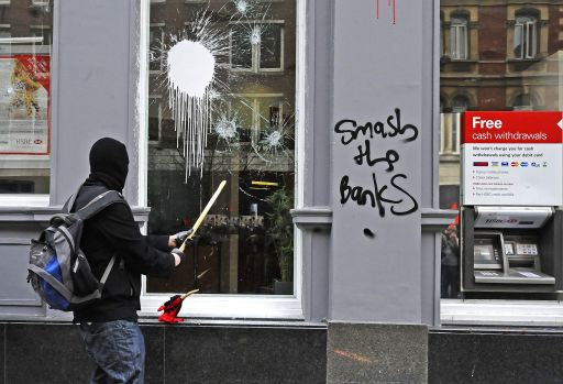 A protester smashes a window at a HSBC bank branch, during a Trade Union Congress (TUC) march against government expenditure cuts, in London, on March 26, 2011. Hundreds of thousands of demonstrators marched in London Saturday in protest at the government's austerity measures, amid a heavy police presence that failed to stop outbreaks of violence. AFP PHOTO/Carl de Souza