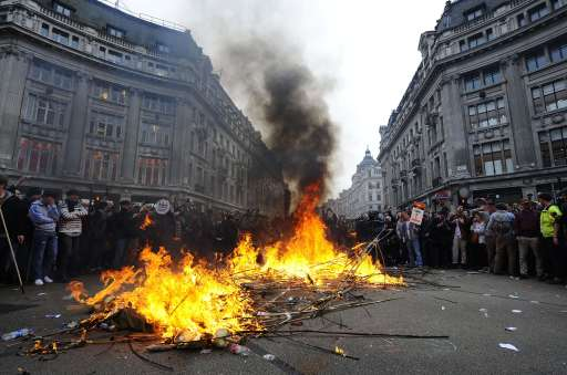 Activists start a fire at Oxford Circus during a Trade Union Congress (TUC) march in London on March 26, 2011. Hundreds of thousands of people from all over the United Kingdom took part in the march to protest against government cuts. AFP PHOTO/Carl de Souza