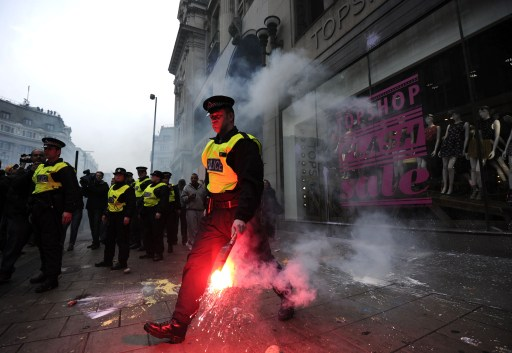 Police clash with protesters outside the Topshop store in central London, during a mass demonstration against government financial cuts, on March 26, 2011. Tens of thousands marched through London today in a demonstration against the government's austerity measures, amid a heavy police presence that failed to stop outbreaks of violence.AFP PHOTO / CARL COURT