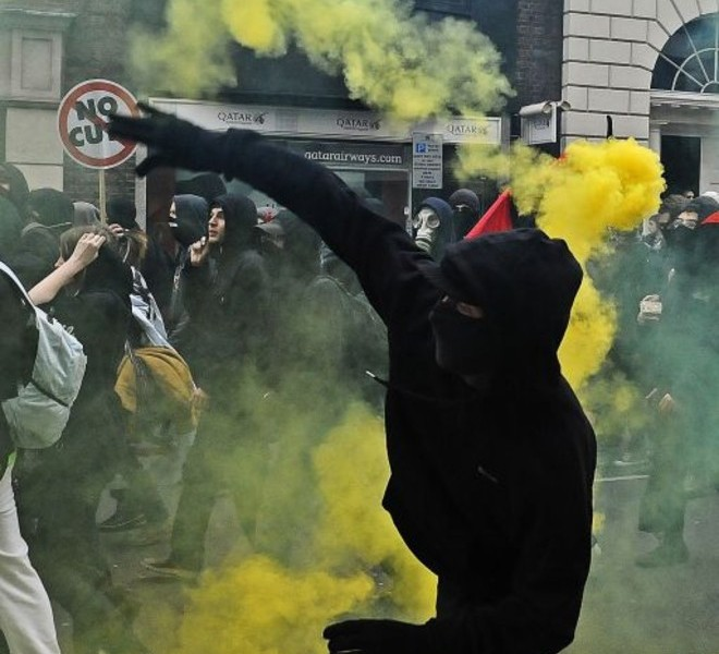 A protester throws a yellow smoke bomb during a Trade Union Congress (TUC) march against government expenditure cuts, in London, on March 26, 2011. Hundreds of thousands of demonstrators marched in London today in protest at the government's austerity measures, amid a heavy police presence that failed to stop outbreaks of violence. AFP PHOTO/Carl de Souza