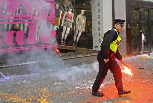 A policeman removes a red flare, which was thrown at a shop, during a Trade Union Congress (TUC) march in London on March 26, 2011. Hundreds of thousands of people from all over the United Kingdom took part in the march to protest against government cuts. AFP PHOTO/Carl de Souza