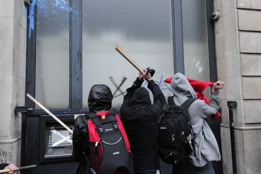 Protesters attack an ATM during a mass demonstration against government financial cuts, in central London, on March 26, 2011. Hundreds of thousands of demonstrators marched in London Saturday in protest at the government's austerity measures, amid a heavy police presence that failed to stop outbreaks of violence. AFP PHOTO / CARL COURT