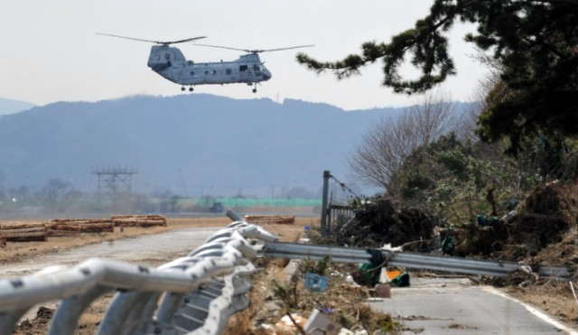 A motorist drives past a boat that was forced under a flyover by the recent tsunami, in Miyako, Iwate prefecture on March 27, 2011. Two weeks after a giant earthquake hit and sent a massive tsunami crashing into the Pacific coast, the death toll from Japan's worst post-war disaster topped 10,000 and there was scant hope for 17,500 others still missing.       AFP PHOTO / ROSLAN RAHMAN
